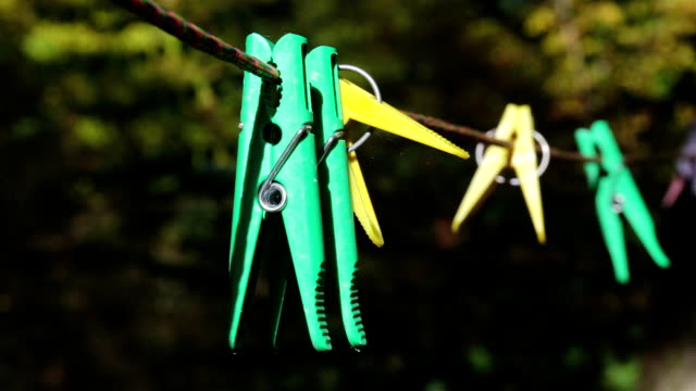 Clothespins hang on a clothesline.