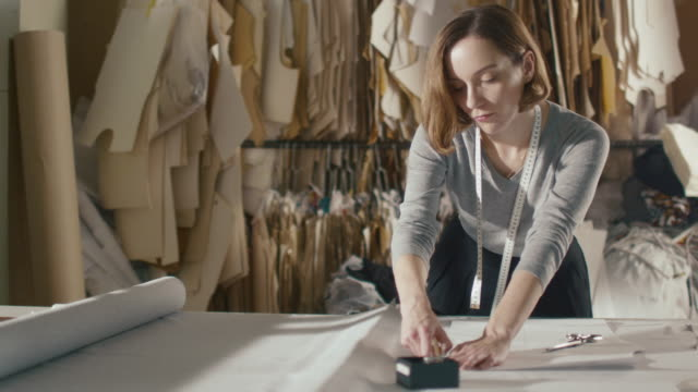 clothing designer is working with measurements on a studio table. - tailor working video stock e b–roll