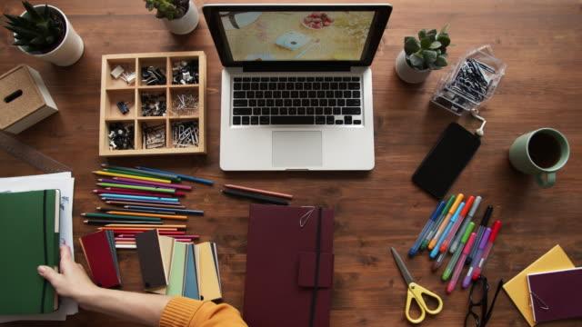 stockvideo's en b-roll-footage met kleding ontwerper tiding up werkplek - opruimen