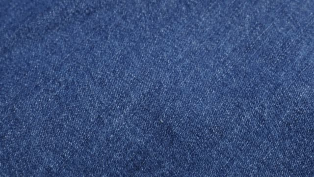 clothing fabric of blue high quality denim details and texture tilting 4k 2160p 30fps ultrahd video - dugaree jeans cloth in blue color gathers slow tilt 4k 3840x2160 uhd footage - jeans video stock e b–roll