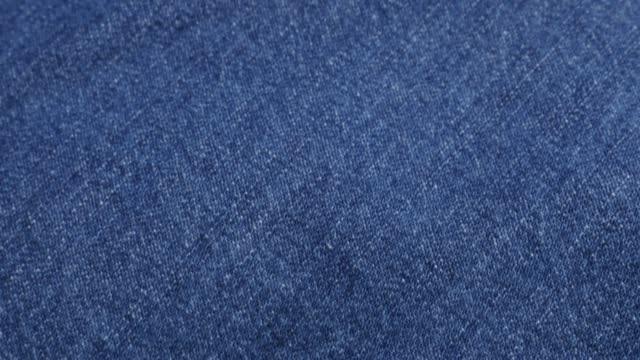 clothing fabric of blue high quality denim details and texture tilting 4k 2160p 30fps ultrahd video - dugaree jeans cloth in blue color gathers slow tilt 4k 3840x2160 uhd footage - dżinsy filmów i materiałów b-roll
