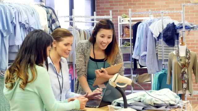 Clothing store employees work together on inventory video