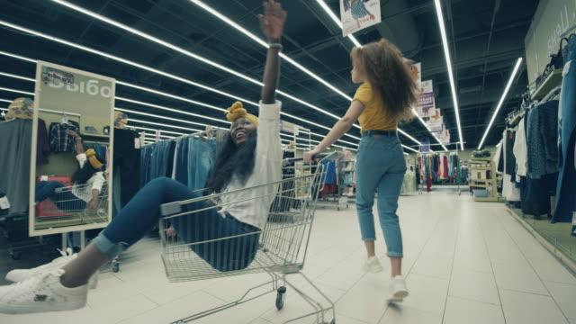 vídeos de stock, filmes e b-roll de loja de roupas com duas mulheres sorridentes brincando - amizade feminina