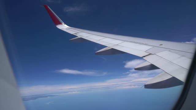 clouds and sky as seen through window of airplane - skrzydło samolotu filmów i materiałów b-roll