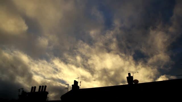 chmury o zachodzie słońca dmuchane na dachy i kominy - osiedle mieszkaniowe filmów i materiałów b-roll