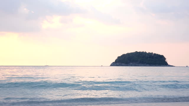 Clouds drift above tranquil sea, at sunrise video