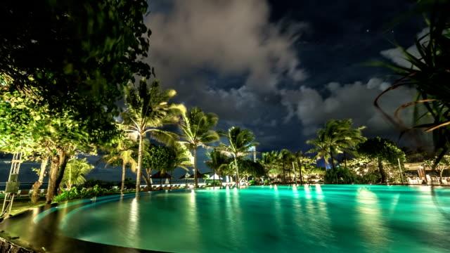 Nuages flottent au-dessus de la piscine illuminée de nuit sur fond de palmiers et la mer. FullHD Timelapse - Bali, Indonésie - Vidéo