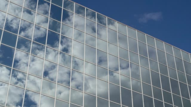 Clouds floating across the blue sky are reflected in the windows of a tall glass building on a sunny day. Concept. 4K