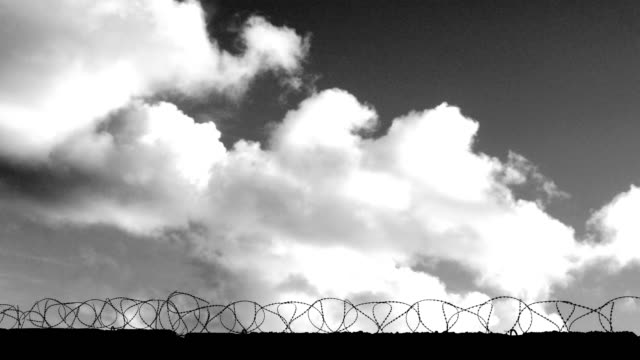 vídeos de stock e filmes b-roll de clouds fly over the fence with barbed wire (black and white) (time lapse) - cercado