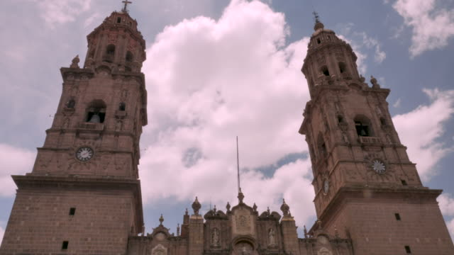 Clouds move between two bell towers of the Morelia Cathedral church in Clouds move between the two bell towers of the Morelia Cathedral church in church architecture stock videos & royalty-free footage