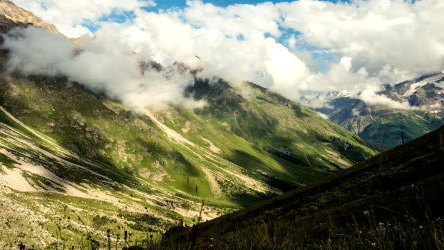 clouds moving above mountain valley. caucasus mountains timelapse - passo montano video stock e b–roll