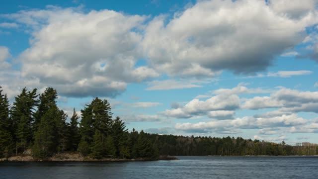 vidéos et rushes de nuages se déplaçant au-dessus d'un lac à distance - nord