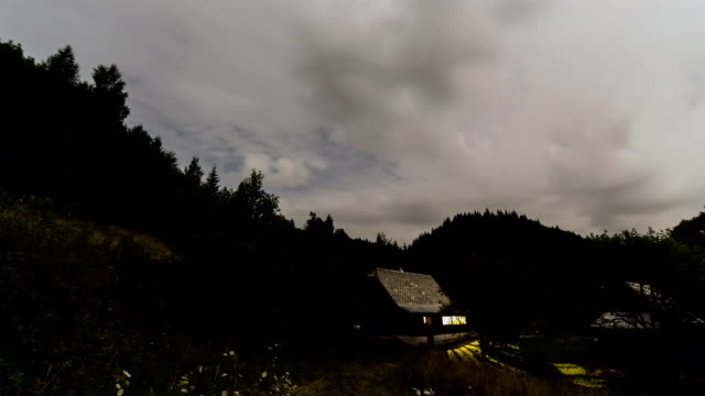 Clouds moving over cottage at night time lapse. Romantic evening in wood cabin video
