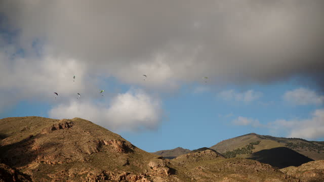 Clouds over mountains and many paragliders flying in sky. Timelapse video