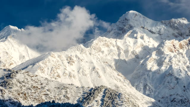 Clouds over the snow-capped peaks of the mountains video