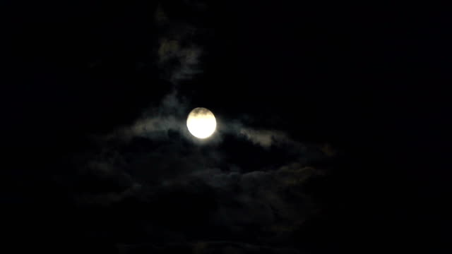 Clouds passing by moon at night. Full moon at night with cloud real time. Details on surface visible video