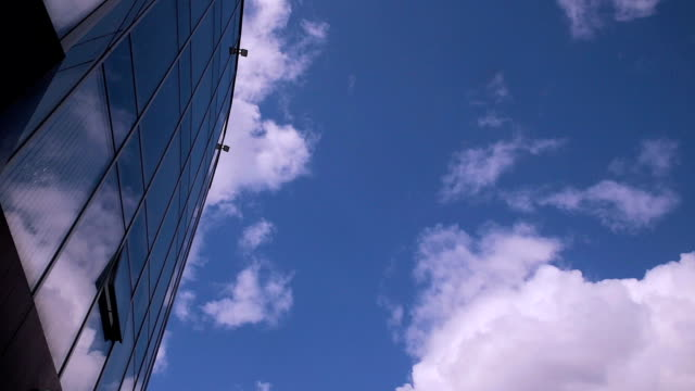 Clouds refelected in modern office building. Timelapse video