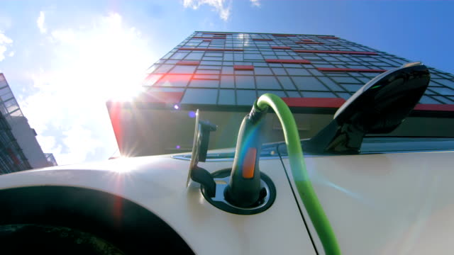 HD TIME LAPSE: Cloudscape Over An Electric Car HD1080p: TIME LAPSE shot of a cloudscape over an electric smart car charging at the charging station in the financial district in the city. electrical equipment stock videos & royalty-free footage