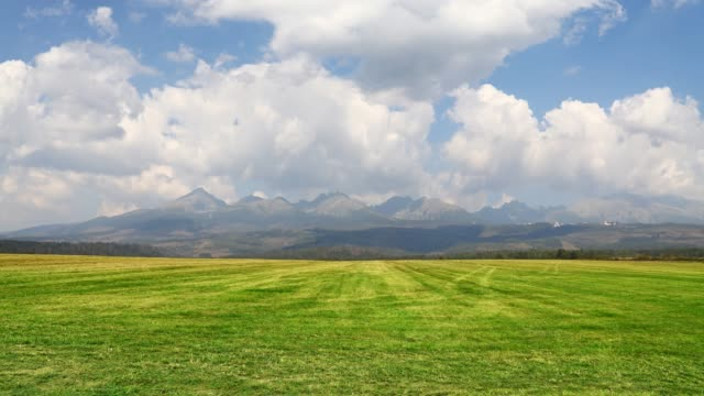 Cloudscape over green field and mountains