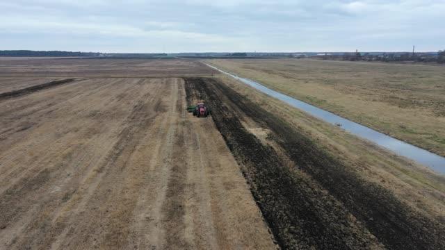 bewölkter tag nach regen. landmaschinen auf dem feld. landwirtschaftliche landschaft aus der luft. traktor auf einem gepflügten feld. landwirtschaftliche sefornung für die anpflanzung von gemüse. traktor macht furchen auf dem feld - aerial view soil germany stock-videos und b-roll-filmmaterial