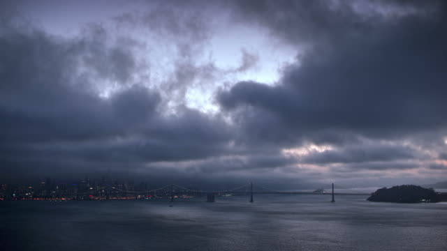 AERIAL Cloudy San Francisco Bay with the Bay Bridge at dusk