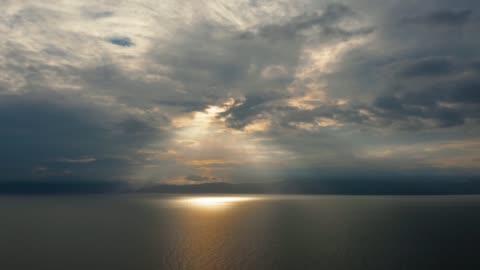 vidéos et rushes de ciel nuageux au-dessus de la mer pendant le coucher du soleil - ciel couvert