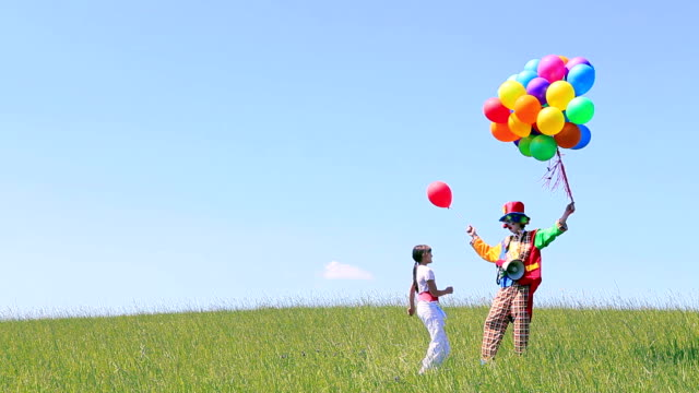 Clown and girl with balloons on field video