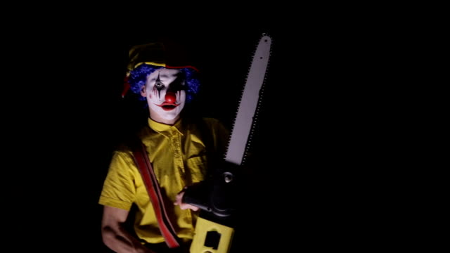 a clown comes out of the dark with a chainsaw. - motosega video stock e b–roll