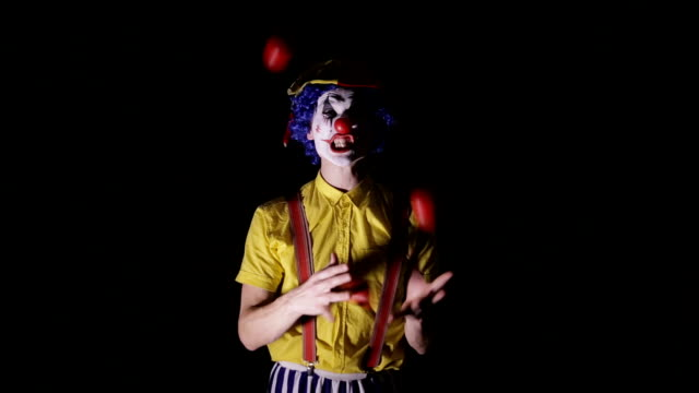 a clown juggles red apples and shows his teeth. - circus стоковые видео и кадры b-roll