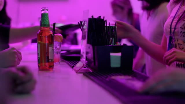 Club guests buying drinks at bar counter, paying by card video