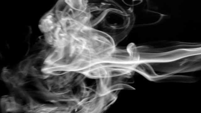 Clubs of white smoke pulsing on a black background. Beautifully video