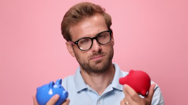 clueless young man wearing glasses, holding piggy banks and examining, pondering and shrugging on pink background