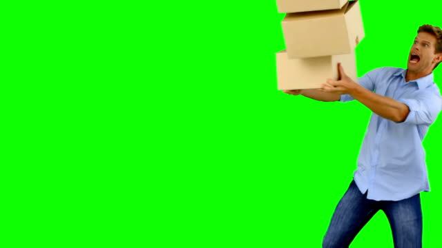 Clumsy man dropping boxes down on green screen video