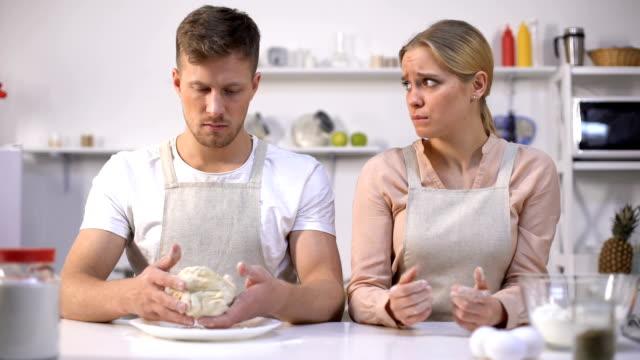 неуклюжий человек растяжения тесто, глядя на жену, пара испытывает трудности с изготовлением торта - baking стоковые видео и кадры b-roll