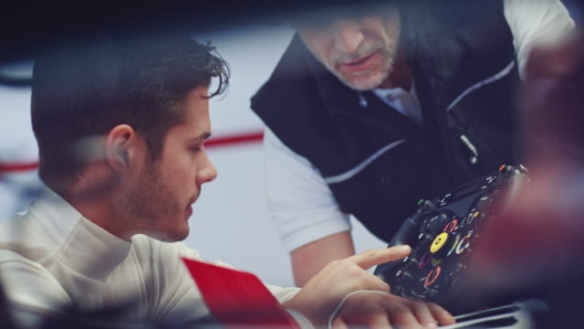 Coach and racer discussing over steering wheel