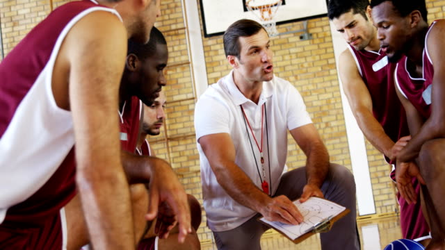 coach explaining game plan to basketball players - allenatore video stock e b–roll