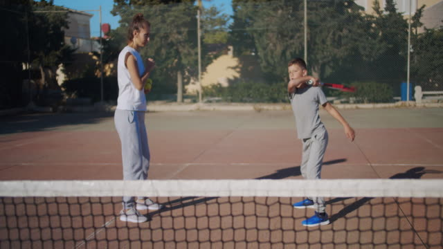 Coach girl teaches the boy how to beat the tennis balls while training at the sports court. The woman throws the ball up, the guy beats his racket