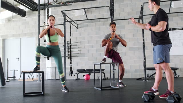 Coach Guiding Male and Female Athletes Doing Box Jumps video