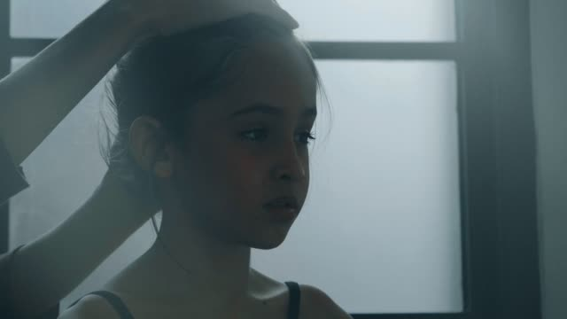 Coach helping little ballerina to tie her hair - Stock video video