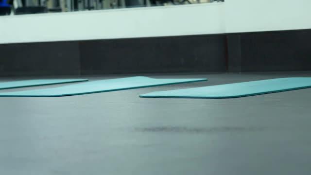 coach puts on a floor mat for fitness - спортивный бюстгальтер стоковые видео и кадры b-roll