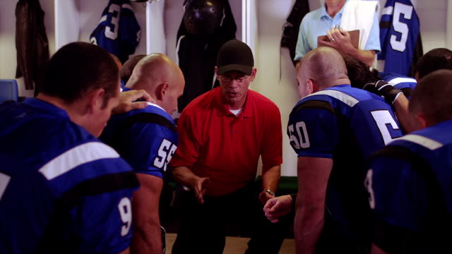 Coach talks to team in locker room -Uberstock- HD 1080p-  Football players sit around their coach and listen to his advice on their play.  Medium shot. coach stock videos & royalty-free footage
