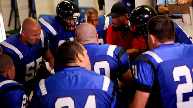 coach parla di squadra in spogliatoio - allenatore video stock e b–roll