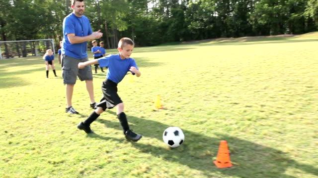 vídeos y material grabado en eventos de stock de entrenador de fútbol infantil equipo de ejercicios de práctica - felicitar