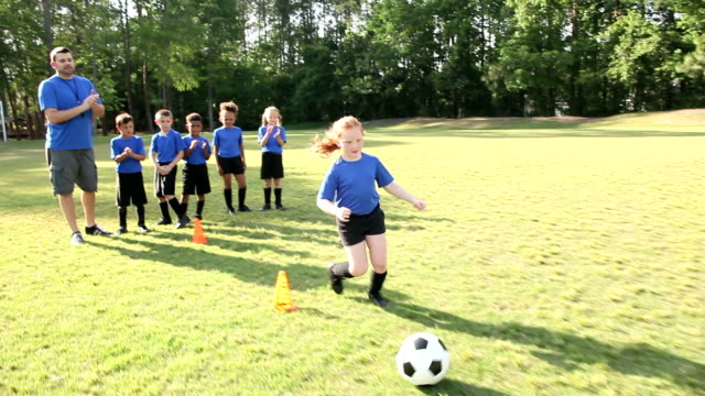 Coach with children's soccer team practicing drills video