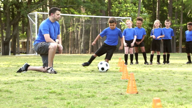 Coach with children's soccer team practicing drills A man coaching a boys and girls soccer team, doing practice drills. A mixed race boy kicks a soccer ball, controlling it through a line of cones as the coach and teammates watch and then clap. practice drill stock videos & royalty-free footage