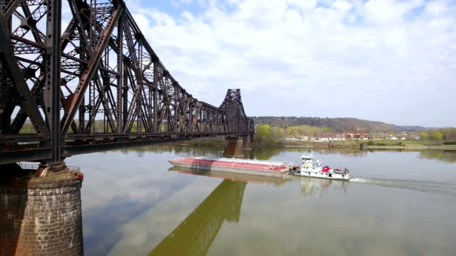 coal barge travels on ohio river under railroad bridge - chiatta video stock e b–roll