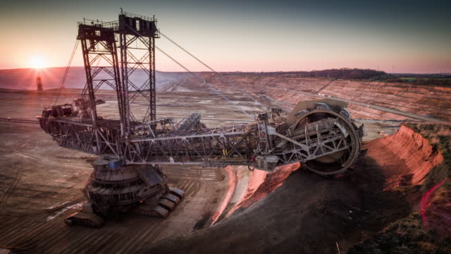Coal Mining, Lignite Surface Mine - AERIAL Aerial shot of a large bucket wheel excavator excavating soil an open pit lignite mine in Germany at sunset. mining natural resources stock videos & royalty-free footage