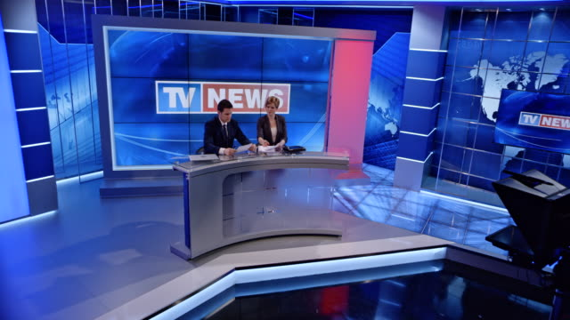 CS Co-anchors standing at the desk in the studio as the lights go on and they starts the evening news video