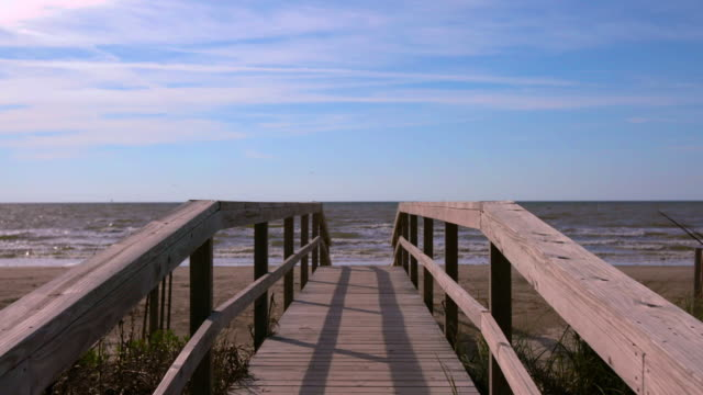 Coastal beach in Galveston, Texas. Push-in slider shot of a wooden bridge leading you to the Gulf of Mexico.