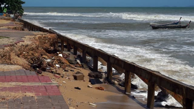 Coastal Erosion due to Extreme Weather The Ocean has encroached on the sea wall and eroded its defences.  Coastal erosion is a significant environmental issue, which is compounded by global warming causing rising sea levels.  Footage taken in Ko Lanta, Krabi province, Thailand. coastal feature stock videos & royalty-free footage